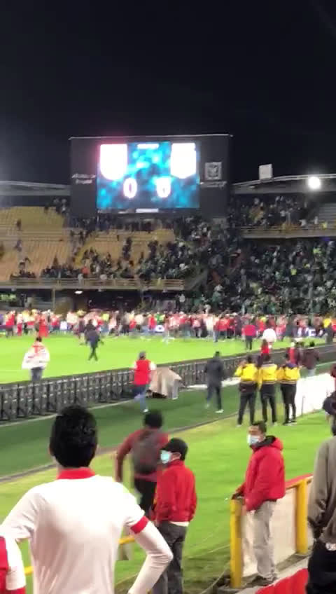 First game with fans in Colombia after 513 days and absolute chaos, HT it's kicked off with dozens spilling on pitch as barra groups from both Santa Fe and Atlético Nacional go looking for a fight, one supporter is on critical state
